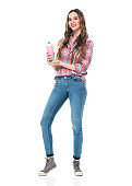 Caucasian young women standing in front of white background wearing jeans and holding milkshake