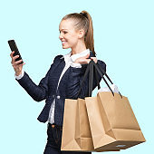 Generation z female shopaholic standing in front of colored background wearing blazer and holding bag and using smart phone