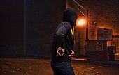 Pacific islander ethnicity young male criminal wearing hooded shirt and holding weapon and using gun