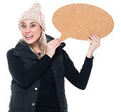 Caucasian female presenter in front of white background wearing jacket and holding thought bubble