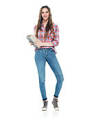 Caucasian young women university student standing in front of white background wearing jeans and holding book