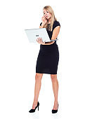 Caucasian female business person standing in front of white background wearing businesswear and using computer