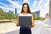 African-american ethnicity young women businesswoman standing who is outdoors wearing business casual and using computer