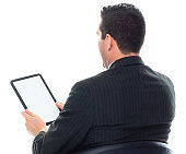 Caucasian male manager in front of white background wearing businesswear and using digital tablet