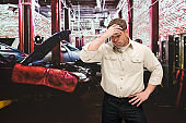 Caucasian male manual worker repairing at the auto repair shop wearing jeans