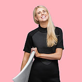 Caucasian female in front of colored background wearing wetsuit and using surfboard