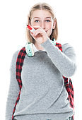 Generation z female teacher standing wearing sweater and holding bag and using pen