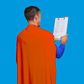 Hero standing in front of blue background wearing costume and holding contract