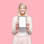 Caucasian female businesswoman standing in front of colored background wearing businesswear and using touch screen