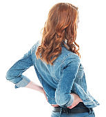 Caucasian female bending over in front of white background wearing jacket