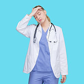 Caucasian female doctor standing in front of blue background wearing lab coat