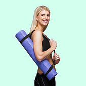 Caucasian female ready for yoga wearing bra and using exercise mat