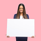 African-american ethnicity young women presenter standing in front of colored background wearing jacket and holding sign