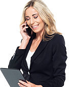 Caucasian female business person standing in front of white background and using mobile phone