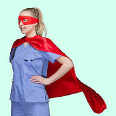 Caucasian young women superhero standing in front of colored background wearing cape - garment