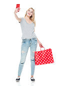 Generation z female photography standing wearing canvas shoe and holding bag and using smart phone