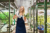 Caucasian female standing at the farm in the greenhouse wearing apron and holding recreational drug