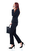 Caucasian female business person walking in front of white background wearing businesswear and holding purse and using mobile phone