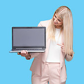 Caucasian young women presenter standing wearing businesswear and using laptop