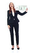 Caucasian female businesswoman standing in front of white background wearing businesswear and holding currency