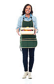 Caucasian young women farm worker standing in front of white background wearing apron and holding box
