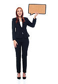 Caucasian female business person standing in front of white background wearing businesswear and holding thought bubble