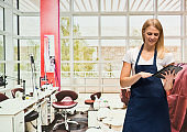 Caucasian young women owner standing at the nail salon wearing apron and using digital tablet