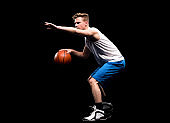 Caucasian young male sleeveless crouching in front of black background wearing tank top and holding basketball - ball and using sports ball