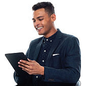 African-american ethnicity young male businessman in front of white background wearing businesswear and using digital tablet