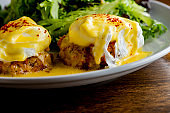 Eggs Benedict. Poached eggs w/ potato hash served in a cast iron skillet. English muffin. eggs, country ham, melted cheese, & homemade hollandaise sauce. Classic French or American cuisine favorite.