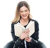 Caucasian female student in front of white background wearing leather jacket and holding book