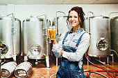 Young women entrepreneur at the food processing plant wearing bib overalls and holding ale