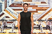 Caucasian male sleeveless spinning at the health club in the gym wearing tank top and being active with sports training and using exercise bike