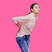 Latin american and hispanic ethnicity female standing in front of colored background wearing jeans