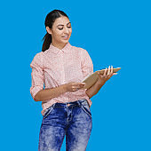 Latin american and hispanic ethnicity young women standing in front of blue background wearing pants and holding paperwork