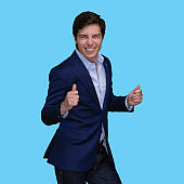 Caucasian young male exercising in front of blue background wearing jacket