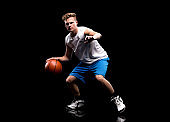 Caucasian teenage boys sleeveless crouching in front of black background wearing sports shoe and holding basketball - ball and using sports ball