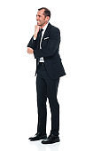 Caucasian young male standing in front of white background wearing businesswear