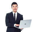 Chinese ethnicity male manager standing in front of white background and using laptop