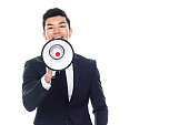 East asian ethnicity male businessman standing in front of white background and holding megaphone