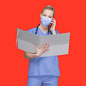 Caucasian female standing in front of colored background wearing surgical mask and holding ring binder and using mobile phone