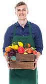 Young male farmer standing in front of white background wearing apron and holding fruit