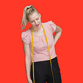 Caucasian female tailor standing in front of colored background wearing pants and using tape measure