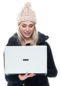 Caucasian young women sleeveless standing wearing sweater and using computer