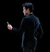 East asian ethnicity young male businessman in front of black background wearing businesswear and using mobile phone