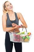 Generation z teenage girls exercising wearing leggings and holding shopping basket