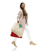 Caucasian female walking in front of white background wearing warm clothing and holding purse