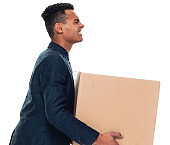 African ethnicity male businessman bending over in front of white background wearing smart casual and holding box