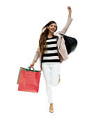 Young women shopaholic jumping in front of white background wearing blazer and holding shopping bag