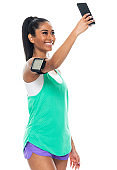 Generation z young women photography standing in front of black background wearing sports shoe and using smart phone